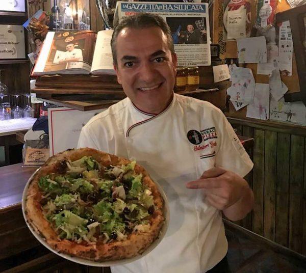 Salvatore Gatta con pizza nel suo locale
