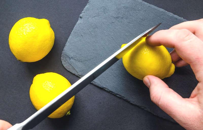 zeste di agrumi taglio dei limoni e mano in primo piano